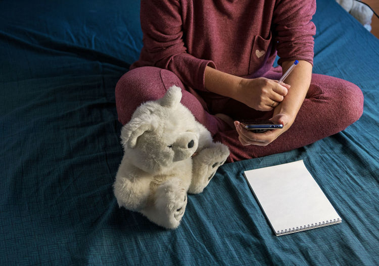 Woman is sitting in a tracksuit on a bed at home. plan your day in notepad.