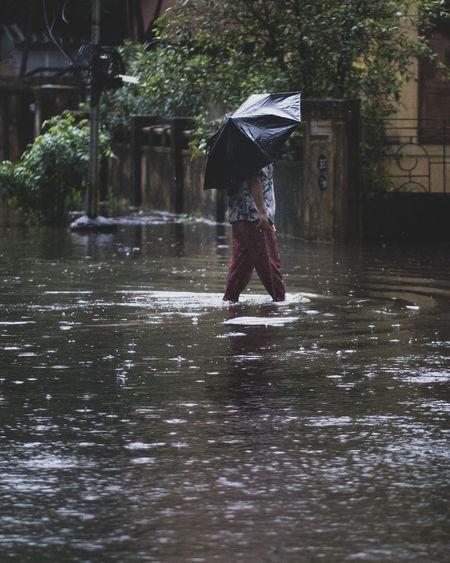 Full length of woman walking in rain during monsoon
