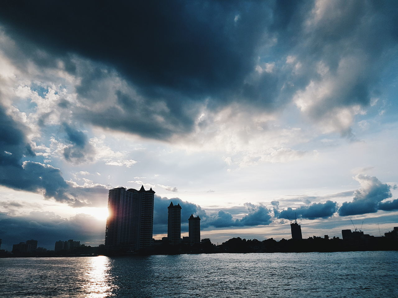 architecture, sky, built structure, cloud - sky, building exterior, water, skyscraper, city, modern, waterfront, outdoors, river, urban skyline, sunset, travel destinations, no people, cityscape, nature, scenics, day, beauty in nature