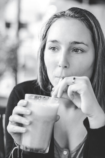 Close-up portrait of young woman holding drink