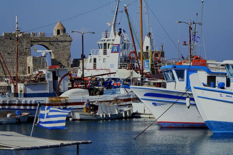 Greek flag against boats moored at harbor