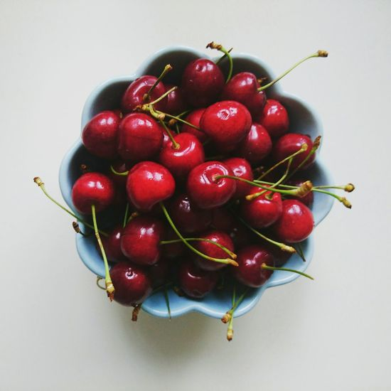 Close-up of cherries over white background