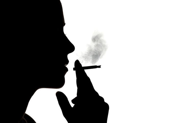 Close-up of silhouette man smoking cigarette against white background