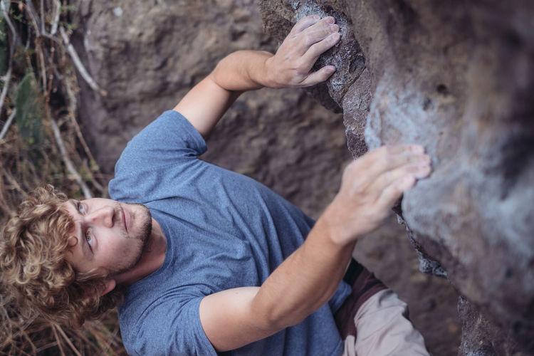 High Angle View Of Man Climbing On Rock