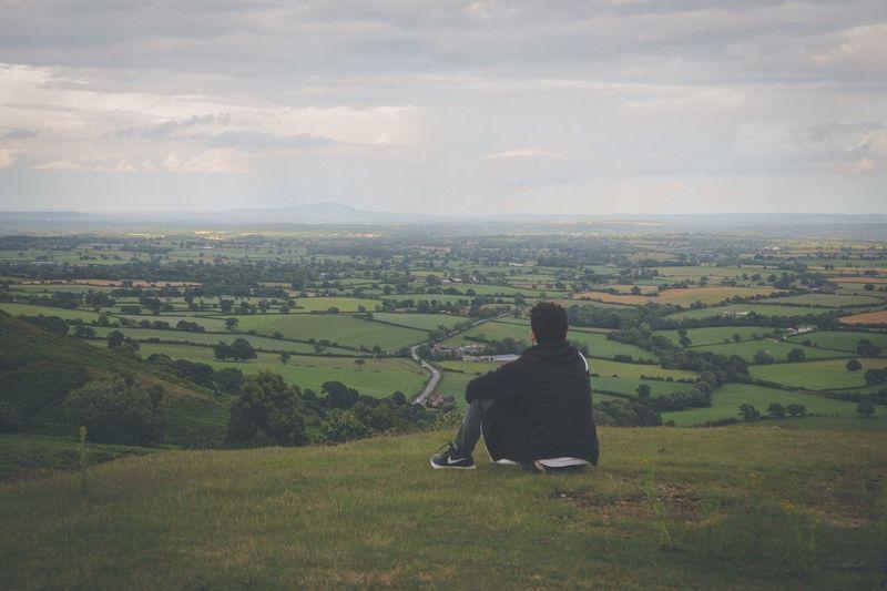 Rear view of man sitting in farm against sky