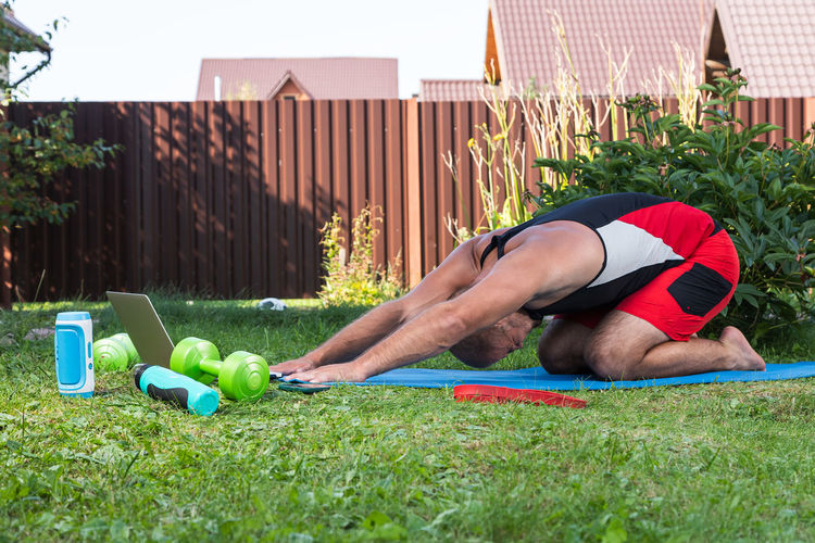 Rear view of man relaxing on grass