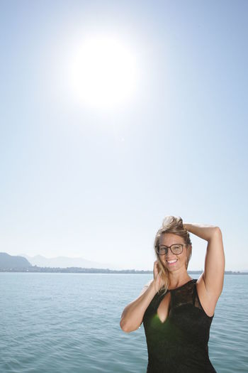 Portrait of smiling woman standing against clear sky