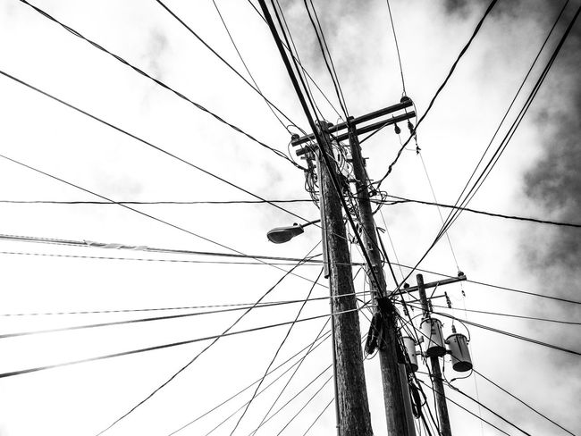 Cable Electricity  Sky Power Line  Low Angle View Cloud - Sky No People Day Pole Outdoors Electrical Equipment Built Structure Chaos