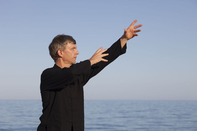 Mature man exercising at beach against clear sky
