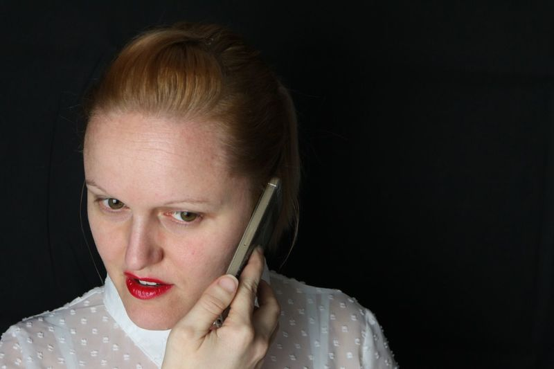 Close-up of young woman talking on smart phone over black background