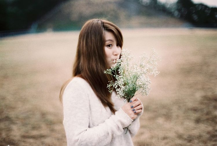 Young Woman Smelling Flowers On Field