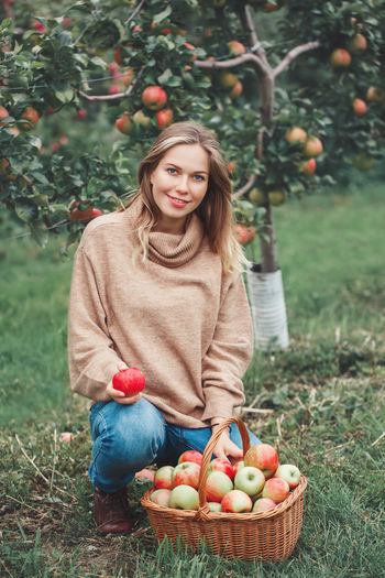 Portrait of smiling pregnant woman picking apples on field