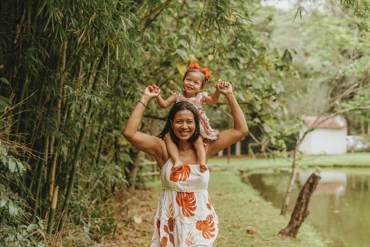 Portrait of smiling mother carrying daughter on shoulder by pond at park