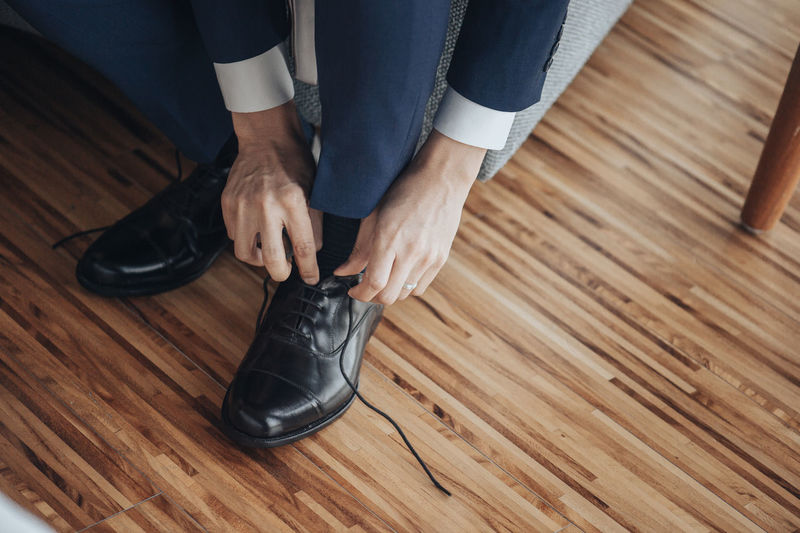 Men are wearing black shoes on wooden up shoes. Shoes ♥ Adult Body Part Bussiness Bussiness Man (: Flooring Hand Hardwood Floor High Angle View Human Body Part Human Foot Human Leg Indoors  Lifestyles Low Section Men One Person Parquet Floor Real People Shoe Sitting Sock Suits  Wood Wood - Material