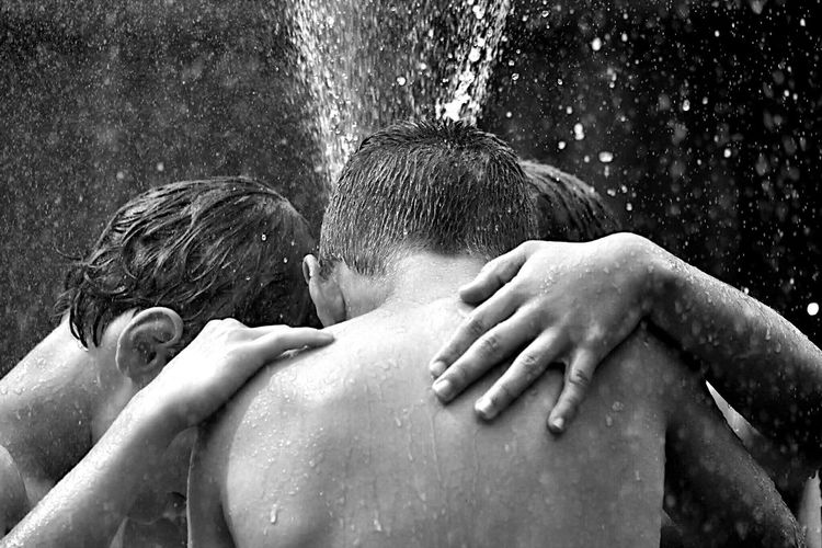 Shirtless friends huddling while enjoying sprinkler in backyard