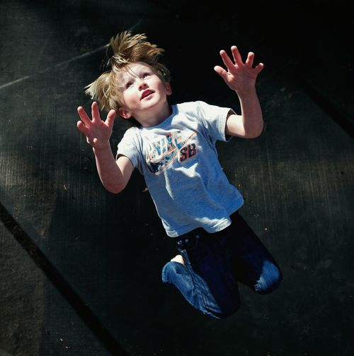 High angle view of boy jumping on trampoline