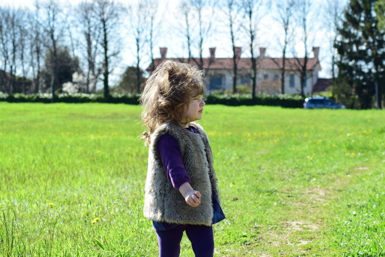 Side view of girl standing on field
