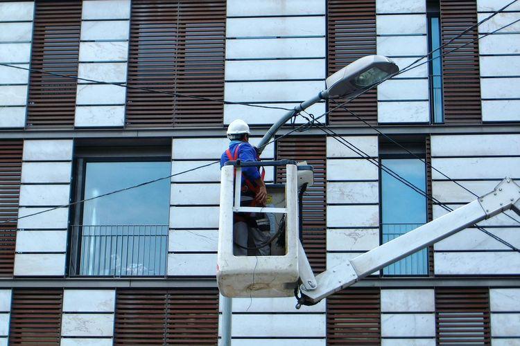 Rear view of worker repairing street light in city