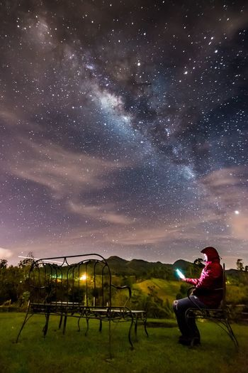 Lost In The Landscape Adult Adults Only Astronomy Beauty In Nature Full Length Galaxy Leisure Activity Lifestyles Men Milky Way Nature Night One Person Outdoors People Real People Scenics Sitting Sky Space Star - Space Tree Young Adult See The Light