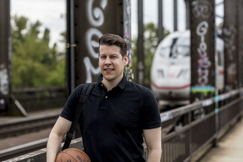 Medium shot of a man holding a basketball in an urban setting. A public transportation train and railway line in the background Adult Basketball Man Public Transportation Sunny Train Tacks Afteroon Casual Clothing Caucasian Day Golf Shirt Good Looking Grafitti Handsome Male Model Outdoors Outside Portrait Posing Railway Smiling Summer Train Urban