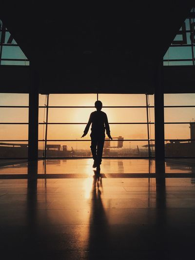 Full length of silhouette boy walking in airport during sunset