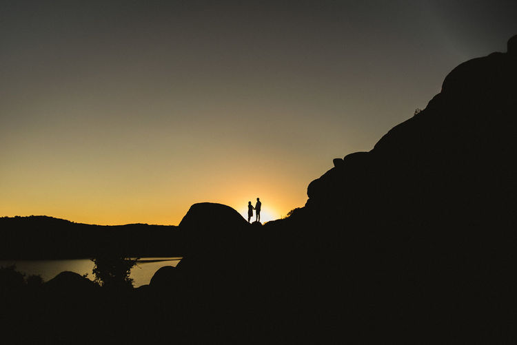 Silhouette Sunset Sky Beauty In Nature Water Copy Space Scenics - Nature Tranquil Scene Tranquility Nature Orange Color Idyllic Clear Sky Rock Mountain Real People Non-urban Scene Rock - Object Outdoors