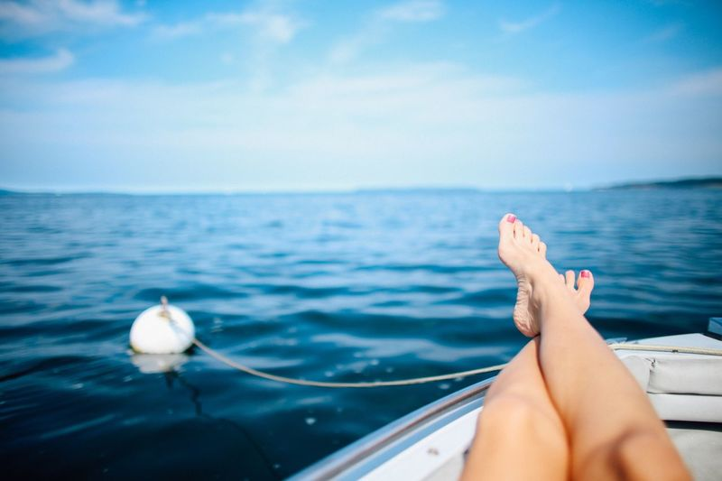 Low section of woman relaxing on boat in sea against sky