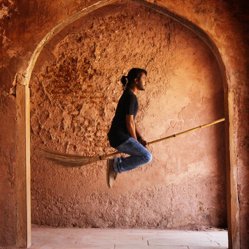 Side view of man levitating on broom against wall