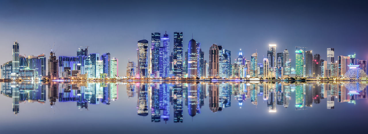 The modern skyline of Doha, Qatar, by night Doha Middle East Modern Panorama Tourist Attraction  Architecture Bay Blue Building Exterior City Cityscape Corniche Illuminated Landmark Modern Night Qatar Reflection Skyscraper Tall Travel Destinations Urban Skyline Water Waterfront Wealth