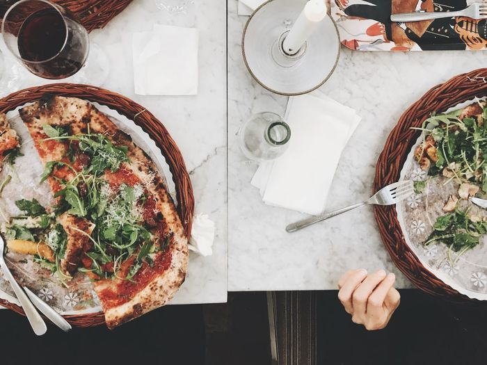 High angle view of pizza served in plate on table at restaurant