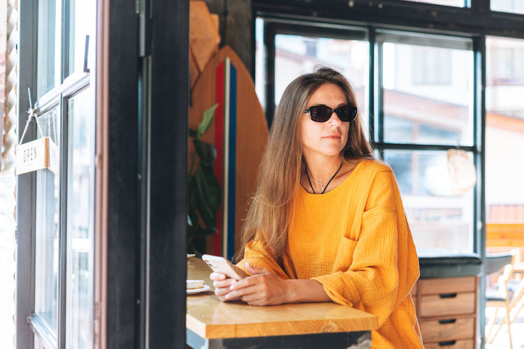 Woman wearing sunglasses on table