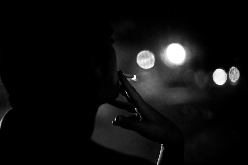 Capture Tomorrow Ash Black And White Black Background Bokeh Burning Cigarettes City Lights Contemplation Fingers Fire Hand Human Body Part Showcase: February Night Photography Reflection Shadow Smoking Urban Window Women Rebel Rebel Learn & Shoot: After Dark Up Close Street Photography