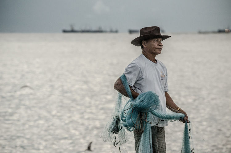 Senior fisherman with fishing net at sea Alone Casual Clothing Countryside Fisherman Fishing Net Folkways Hat Hat Hobby Leisure Activity Life Lifestyles Man Nature Ocean People Portrait Sea Senior Senior Portrait Side View Standing Thailand Vintage Waiting
