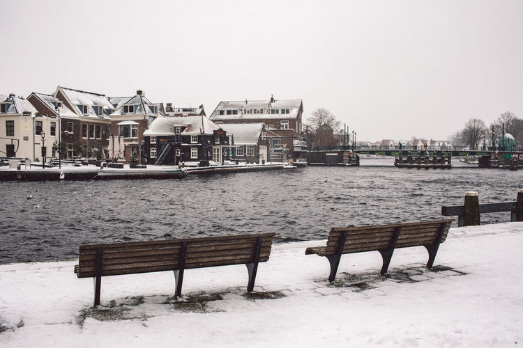 Empty bench by river against buildings during winter