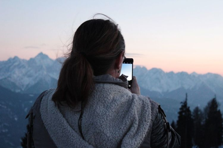 Rear view of woman photographing mountains through phone