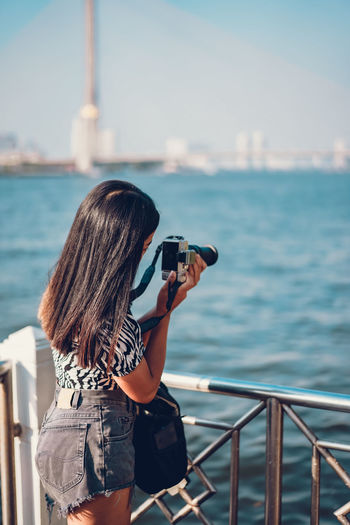 Rear view of woman photographing against sea