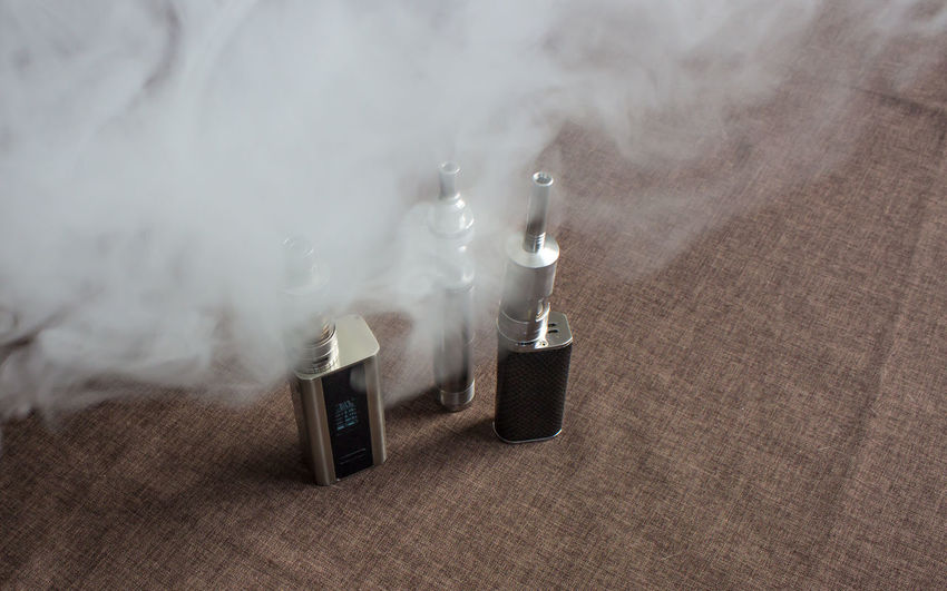 High angle view of electronic cigarettes on table with smoke