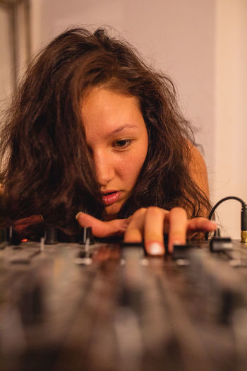 Close-up of fashionable young woman playing music at home