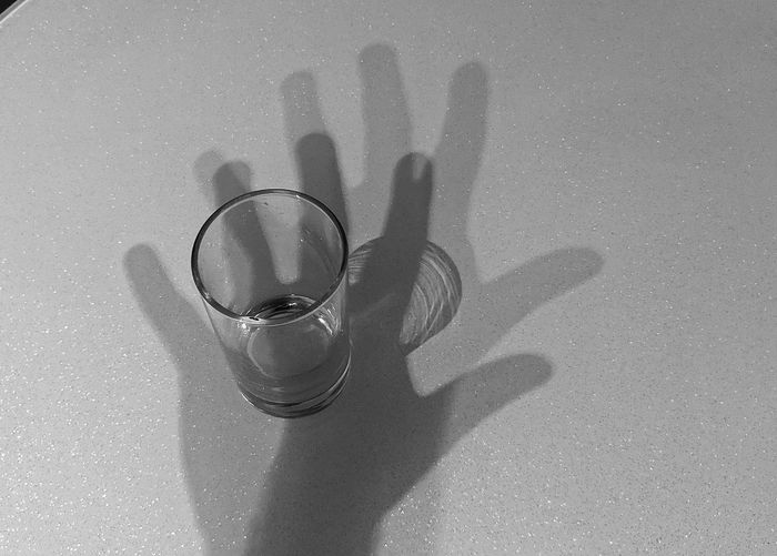 High angle view of hand on glass table