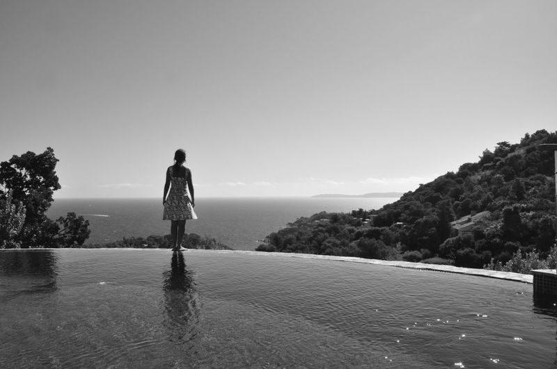 Rear view of woman standing at poolside against sea and sky