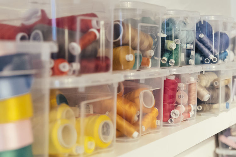 Close-up of multi colored bottles in shelf