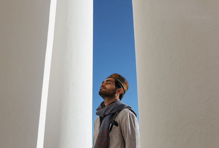 Low angle view of man standing against clear sky
