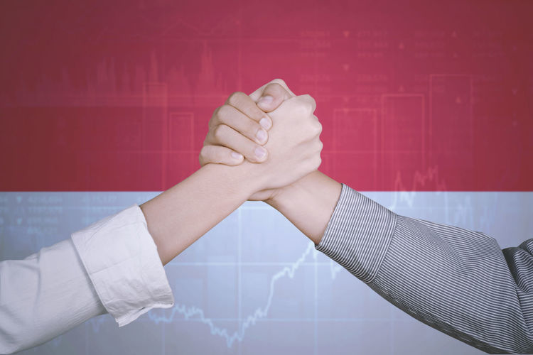 Cropped image of people holding hands against graph