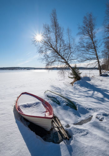 Bright winter day with sunlight, boat and sun beams at lake in Finland Winter Snow Cold Temperature Sky Nature Land Sunlight Day Outdoors Tree Bare Tree Frozen Finland Landscpae Sunbeam Ray Tranquility Beauty In Nature Sunlight Boat White Blizzard Lake Daylight Blue Sky