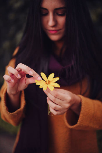 Smiling woman holding flower standing outdoors