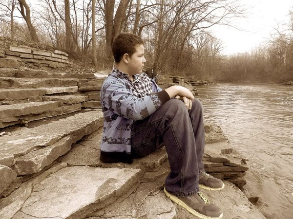 Overlooking the Rouge River Beauty In Nature Blue Boy Casual Clothing Day Full Length Gaze Henry Ford Estate In Thought Leisure Activity The Portraitist - 2016 EyeEm Awards Nature Outdoors Portrait Relaxation Rocks Rouge River Select Color Staring Thinking Tranquil Scene Tranquility Tree Young Adult Young Man