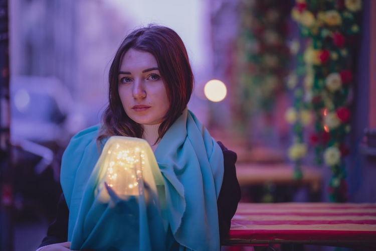 Portrait beautiful woman with blue scarf and glowing jar in city at dusk