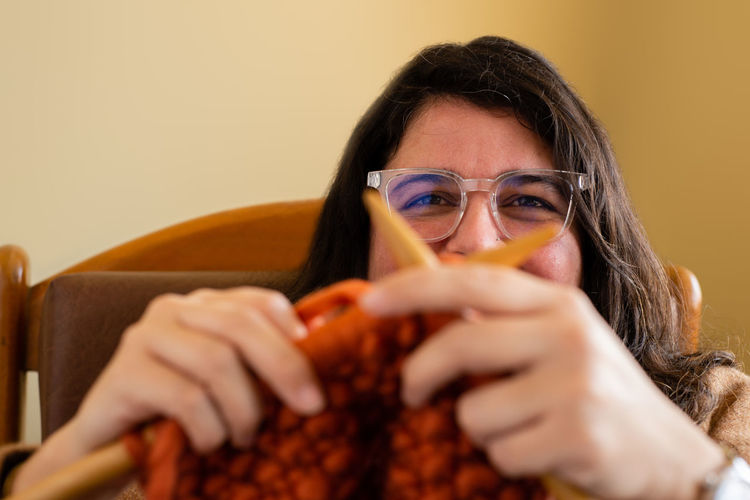 Close-up of woman knitting wool at home