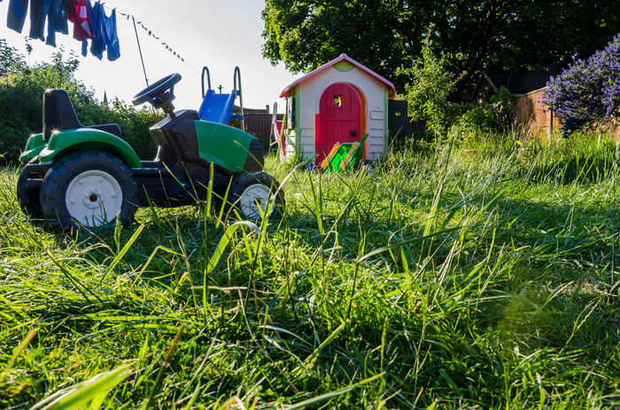 Long grass and garden toys in a back garden. Agricultural Machinery Agriculture Back Garden Combine Harvester Day Field Garden GARDEN TOYS Grass Green Color Growth Lawn Log Grass Nature No People Outdoors Play House Residential Garden Toy Tractor Transportation Tree Washing Line