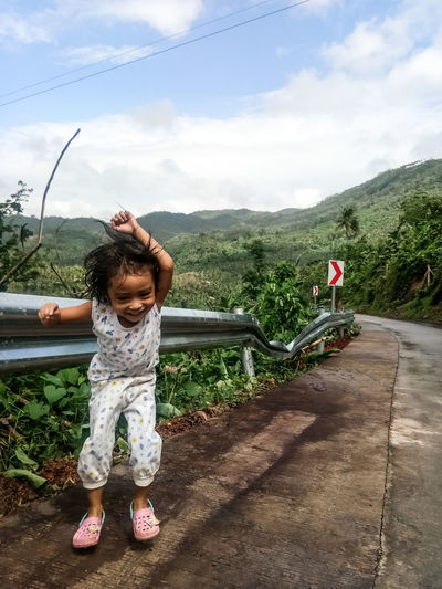 Full length of girl standing on mountain against sky